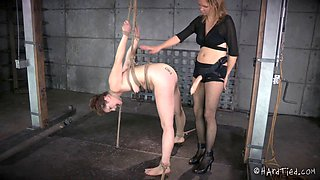 Dominant babe with a strap-on and her prisoner with a sexy body