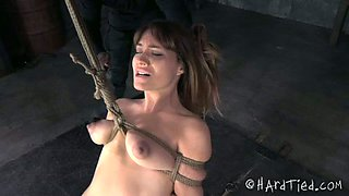 Desirable brunette girl is hanged on her boobs by her black master