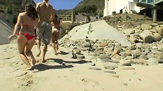 Lucky muscular jerk guy receives a nice blowjob and has sex with two hotties at the beach