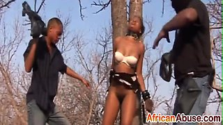 African hottie enjoys getting tied and abused by two studs outdoors.