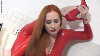 Flexible woman red latex catsuit redhead